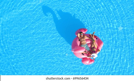 AERIAL TOP DOWN: Young couple in swimsuit sipping cocktails on flamingo floatie
