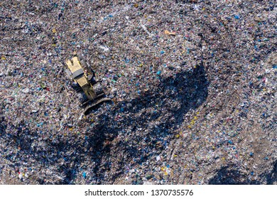 Aerial top drone view of large garbage pile, trash dump, landfill, waste from household dumping site, excavator machine is working on a mountain of garbage. Consumerism and contamination concept