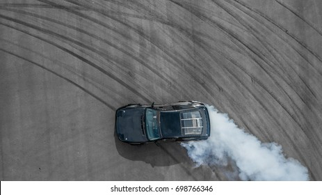 Aerial top professional driver drifting car on asphalt track, Black car tire drift skid mark on road race track with smoke, Black tire mark on street race track, Automobile and automotive concept.