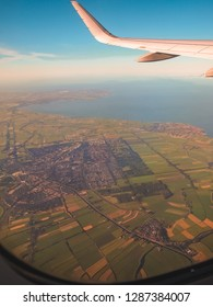 Aerial, or top view from airplane window.  Wing of an airplane flying above Europe.