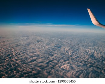 Aerial, or top view from airplane window. Wing of an airplane flying above the clouds - Wanderlust concept