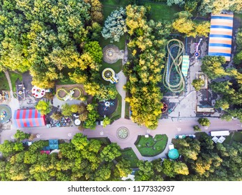 aerial top view of amusement park with attractions and trees at summer morning