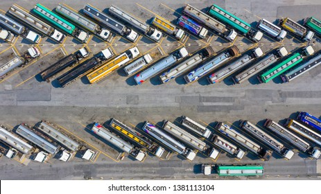 Aerial top view automotive fuel tankers shipping fuel, Semi truck with cargo trailer parking at oil station.