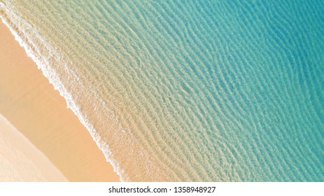 Aerial top view of Beach with shade emerald blue water and wave foam on tropical sea