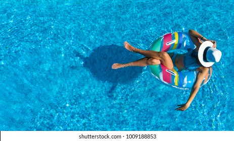 Vista aérea de una hermosa chica en la piscina desde arriba, relájese nadando en el anillo inflable y disfrute de diversión en el agua en vacaciones familiares, centro turístico tropical