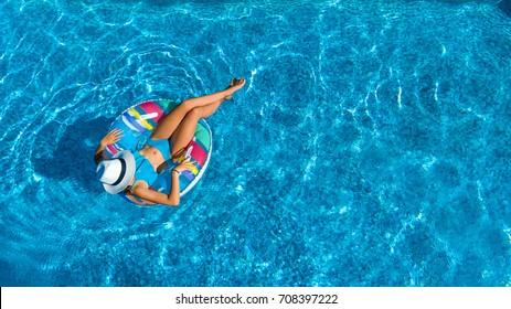 Vista aérea de la cima de una hermosa chica en la piscina desde arriba, relájese nadando en el anillo inflable y diviértase en el agua en vacaciones familiares