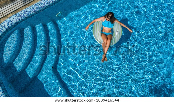 Aerial top view of beautiful girl in swimming pool from above, relax swim on inflatable ring donut and has fun in water on family vacation, tropical holiday resort