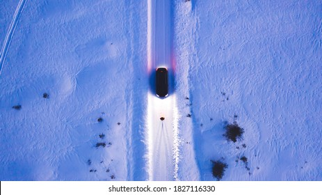 Aerial top view of car on rural area road while headlights are on in winter darkness, bird's eye view of suv vehicle in snowy north lands. Person standing front automobile which lighting the way
