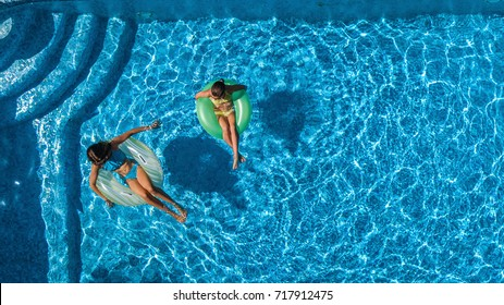 Aerial top view of children in swimming pool from above, happy kids swim on inflatable ring donuts and have fun in water on family vacation