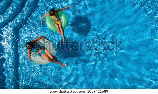 Aerial top view of children in swimming pool from above, happy kids swim on inflatable ring donuts and have fun in water on family holiday vacation on resort