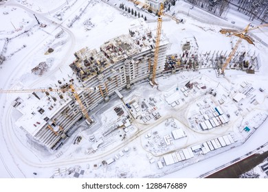 aerial top view of city construction site. tower cranes for building of new apartments under snow in winter
