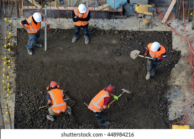 Aerial top view of construction site workers leveling cement in building site