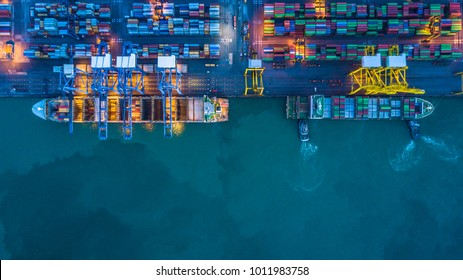 Aerial top view of container cargo ship in import export business logistic at night.