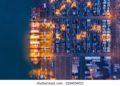 Aerial top view of container cargo ship in the export and import business and logistics international goods in urban city. Shipping to the harbor by crane in Victoria Harbour, Hong Kong City at night.