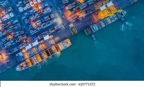 Aerial top view container cargo ship waiting for loading at night, import export business logistic and transportation by ship in open sea.