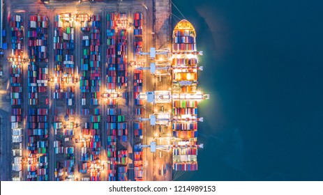 Aerial top view crane shipping container at night, cargo container ship carrying container import and export business logistic and transportation.