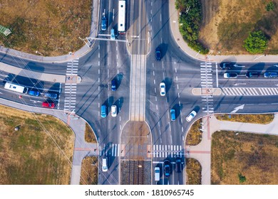 Aerial top view of crossroads with lot of vehicles or car traffic, modern urban intersections and junctions in midtown. Road traffic on crossroad or intersection downtown of European.