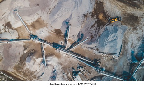 Aerial top view of crushing machinery, conveying crushed granite gravel stone in a quarry open pit mining. Processing plant for crushed stone and gravel. Mining and Quarry mining equipment.