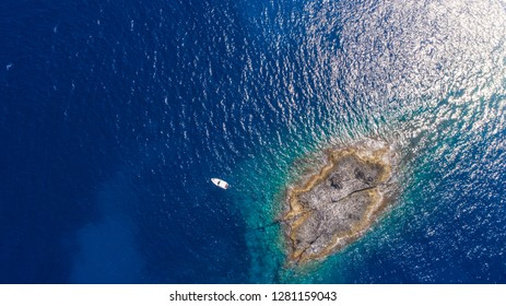 Aerial top view of a deserted island with white boat. Rocky shore of Zannone island near Ponza, Italy. Blue clear water on sunny day.