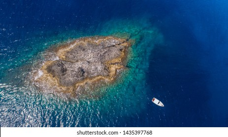 Aerial top view of a deserted island with white boat. Rocky shore of Zannone island near Ponza, Italy. Blue clear water on sunny day. 04