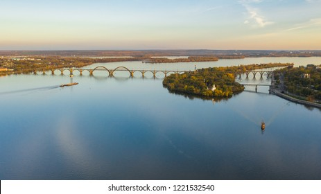 Aerial top view from drone on railway bridge above Dnieper river in Dnipro city. Autumn landscape and cityscape background. (Dnepr, Dnepropetrovsk, Dnipropetrovsk)