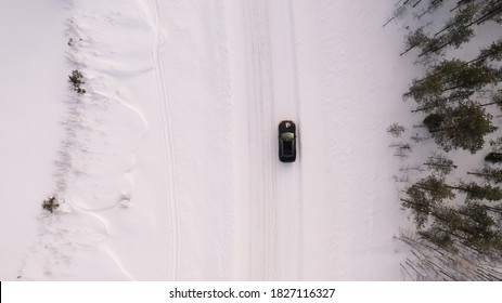 Aerial top view from drone of suv vehicle driving on snowy ice road exploring local landscapes in winter, bird's eye view of automobile car moving on area surrounded by beautiful coniferous forest
