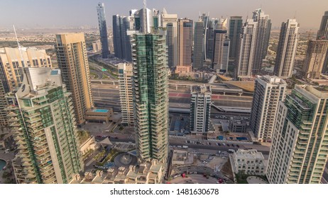 Aerial top view of Dubai Marina and JLT evening timelapse. Promenade and canal with floating yachts and boats before sunset in Dubai, UAE. Modern towers and traffic on the road