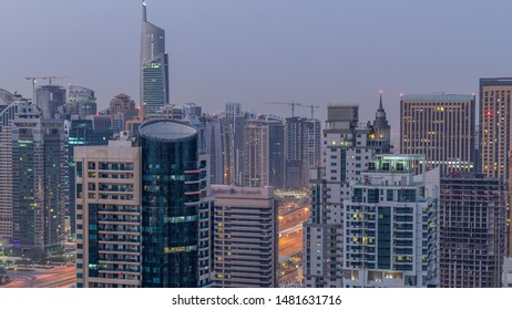 Aerial top view of Dubai Marina and JLT night to day transition timelapse. Skyscrapers before sunrise in Dubai, UAE. Illuminated modern towers and traffic on the road