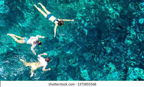 Aerial top view of family snorkeling from above, mother and kids snorkelers swimming in a clear tropical sea water with corals during summer vacation in Thailand
