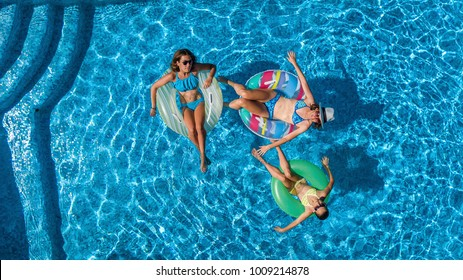 Aerial top view of family in swimming pool from above, happy mother and kids swim on inflatable ring donuts and have fun in water on family vacation, tropical holidays on resort