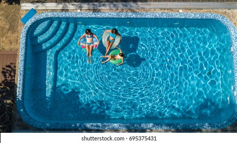 Aerial top view of family in swimming pool from above, mother and kids swim and have fun in water on family vacation in hotel resort