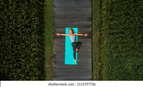 Aerial top view to a female practicing yoga on a mat laying on wooden pathway surrounded by green rice fields