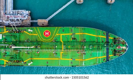 Aerial top view of fuel tanker ship at the port, Oil terminal is industrial facility for storage of oil and gas petrochemical products ready for transport to further storage facilities.