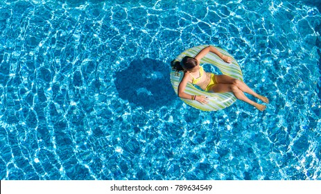 Aerial top view of girl in swimming pool from above, kid swims on inflatable ring donut , child has fun in water on family vacation