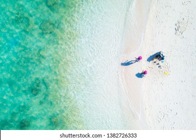 Aerial top view of happy young mum with children building a sandcastle together on tropical shore. Colorful turquoise sea. Peaceful andaman sea at Koh Lipe, Satun, Thailand.