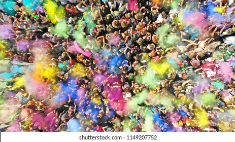 Aerial top view of a Holi Colors Festival. Splash of paint in a crowd of people view above.