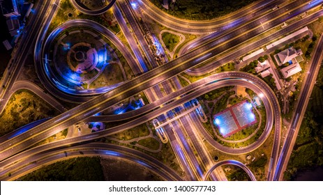 Aerial top view interchange of a city at night, Expressway is an important infrastructure in city, Road interchange in the city at night with vehicle car light movement.