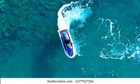 Aerial top view of jet ski cruising in low speed in tropical sapphire clear waters
