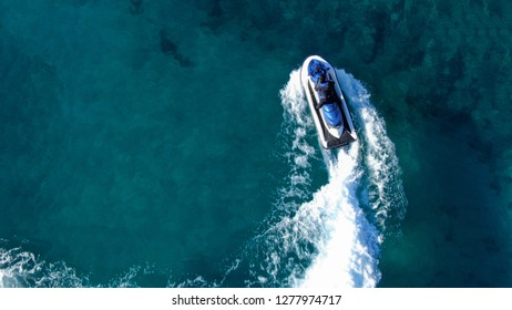 Aerial top view of jet-ski cruising in low speed in mediterranean emerald clear waters