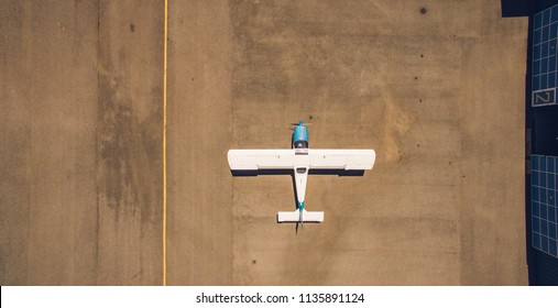 Aerial top view of a light aircraft, preparing for taking off at small countryside airfiled