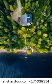Vue aérienne du sommet de la cabane en bois ou de la maison ou du chalet dans la forêt printanière au bord du lac en Finlande rurale