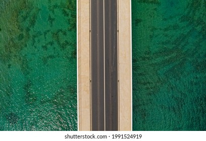 Aerial top view of a long bridge above a sea near Trogir and Split in Croatia. Isolated by the green sea water.