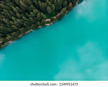 Aerial top view of magically beautiful color water meets the shore with a beautiful fir-tree coniferous forest. Bird's eye view of turquoise reservoir basin, unique place in Natural Protected park