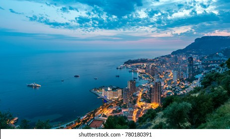 Aerial top view of Monaco from the grand corniche road day to night transition timelapse, Monaco France. Evening illumination. Reflections in water of harbor