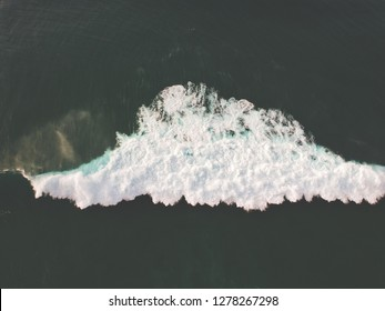 Aerial top view of ocean wave with foam. Drone Photo