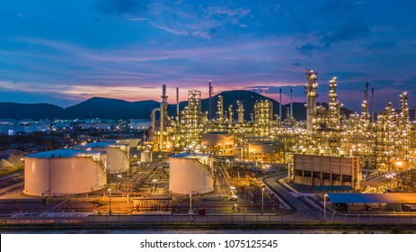 Aerial top view oil and gas chemical tank with oil refinery plant background at twilight.