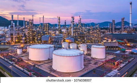 Aerial top view oil and gas chemical tank with oil refinery factory background at twilight.