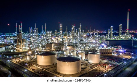 Aerial top view oil and gas tank with oil refinery background at night.