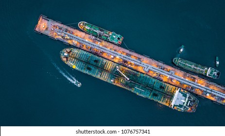Aerial top view of oil tanker ship at the port, Oil terminal is industrial facility for storage of oil and petrochemical products ready for transport to further storage facilities.