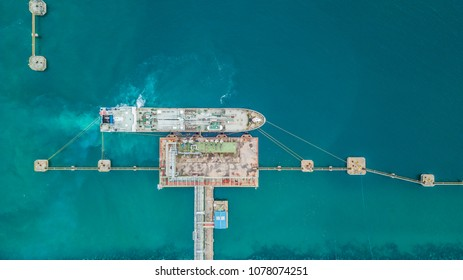Aerial top view of oil tanker ship at the port, Oil terminal is industrial facility for storage of oil and petrochemical products ready for import export business logistic and transportation